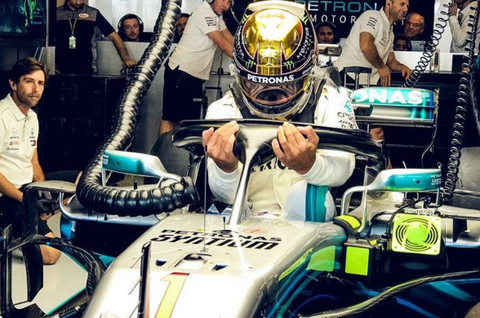 Lewis Hamilton saat bersiap di dalam garasi tim Mercedes jelang mengikuti sesi latihan bebas F1 GP A