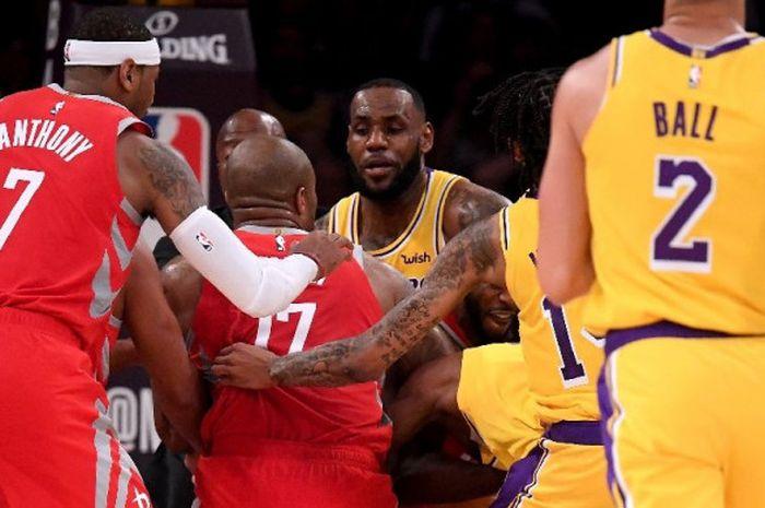 LeBron James (tengah) saat mencoba memisahkan sejumlah pemain saat perkelahian terjadi pada laga musim reguler NBA 2018/19 yang digelar di Staples Center, Minggu (21/10/2018) pagi WIB.