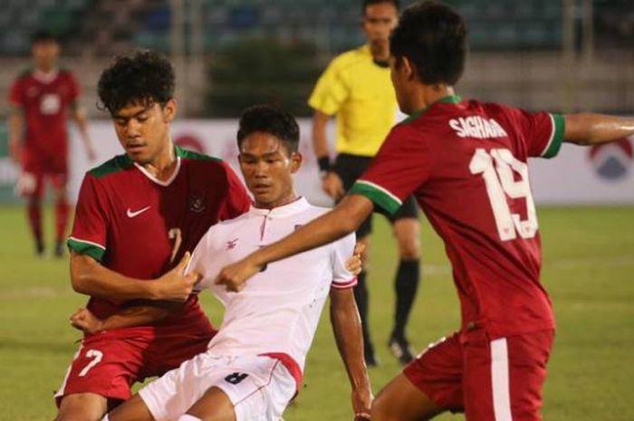 Duo pemain timnas U-19 Indonesia, Muhamad Luthfi Kamal Baharsyah (kiri) dan Hanis Saghara Putra mengapit pilar timnas U-19 Myanmar, Myat Kaung Khant pada laga pertama Grup B Piala AFF U-18 edisi 2017 di Stadion Thuwunna, Yangon, Selasa (5/9/2017) malam.