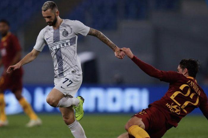 Gelandang Inter Milan, Marcelo Brozovic, menghindari tekel pemain AS Roma, Nicolo Zaniolo dalam laga pekan ke-14 Liga Italia di Stadion Olimpico, Roma, Senin (3/12/2018) dini hari WIB.