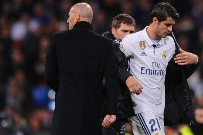 Penyerang Real Madrid, Alvaro Morata (kanan), saat ditarik keluar oleh pelatih Zinedine Zidane dalam duel La Liga kontra Real Betis di Stadion Santiago Bernabeu, Madrid, 12 Maret 2017.