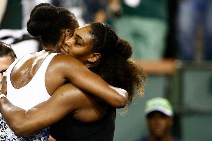 Venus Williams (baju putih) dan Serena Williams (baju hitam) saat berpelukan usai keduanya bertemu p