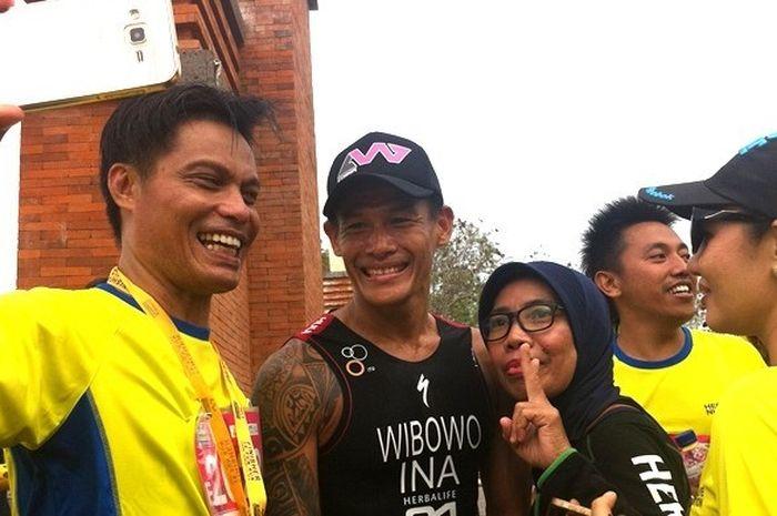 Atlet triathlon Indonesia, Andy Wibowo, diajak foto seusai memenangi Herbalife Bali International Tr