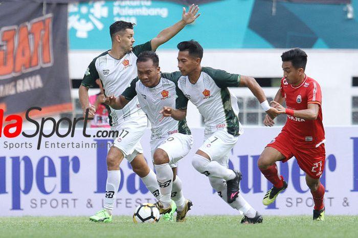 Pemain Persija, Fitra Ridwan mencoba merebut bola dari tiga pilar PS Tira, Dzimitry Rekish, Wawan Febriyanto, dan Ahmad Nufiandani (dari kiri ke kanan) pada laga pekan ke-30 Liga 1 2018 di di Stadion Wibawa Mukti, Cikarang Timur, Kabupaten Bekasi, Sabtu (10/11/2018).