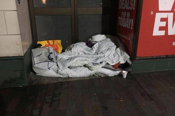 Seorang tunawisma disiram air saat tidur di emperan toko