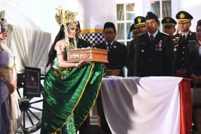 Bupati Purwakarta Dedi Mulyadi menerima bendera Merah Putih dari sosok Nyi Ratu Kidul sebelum diserahkan pada Paskibra yang sudah dikukuhkan.