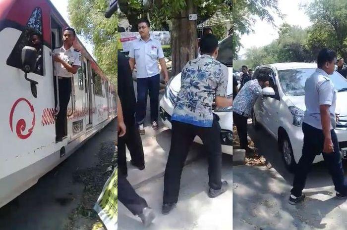 Cuplikan video yang menggambarkan warga tengah berusaha memindahkan mobil yang parkir di atas rel Jalan Slamet Riyadi, Solo, Jawa Tengah.