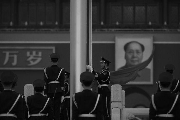 Seorang perwira polisi paramiliter mengumpulkan bendera RRC di depan potret Mao Zedong di Lapangan Tiananmen Beijing.