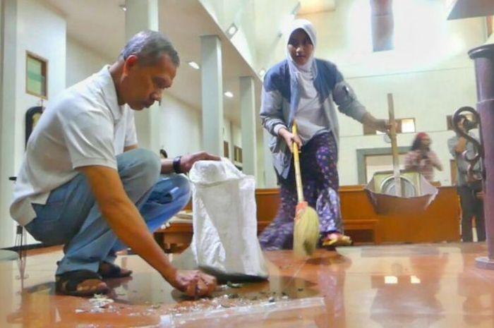 Jirhas Rani (kanan) saat membantu membersihkan Gereja Santa Lidwina di Bedog, Sleman, Yogyakarta, Senin (12/2/2018), dengan seorang warga. Jirhas datang bersama suaminya, Ahmad Muttaqin (tidak tampak dalam gambar)
