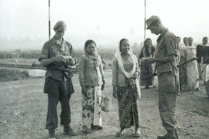 Tentara Belanda sedang memeriksa surat-surat dari perempuan Jawa.