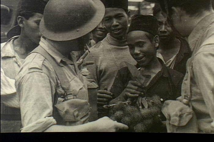 Serdadu Australia sedang bercakap-cakap dengan orang Indonesia yang menjual buah kepada mereka beberapa minggu sebelum Jepang mengakhiri imperium Hindia Belanda.