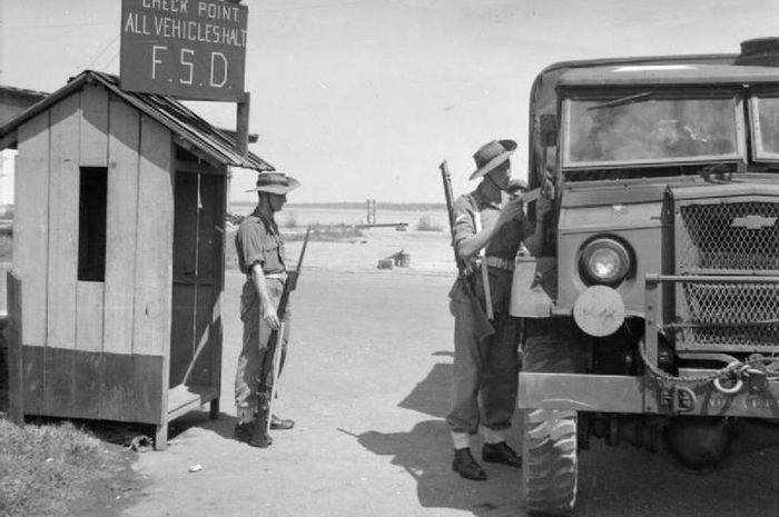 Pos penjagaan tengah memeriksa kelengkapan surat sebuah truk militer, 1945.