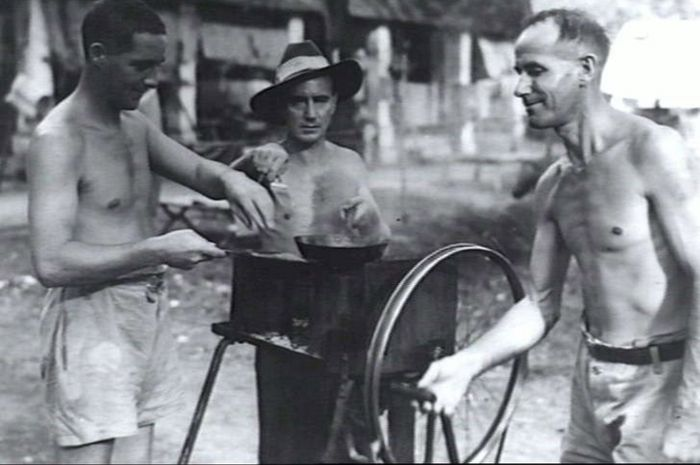 Tiga tawanan perang asal Australia sedang memasak nasi goreng di atas arang membara.