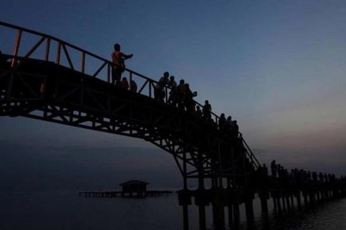 Wisatawan menikmati suasana matahari pagi di Jembatan Cinta.