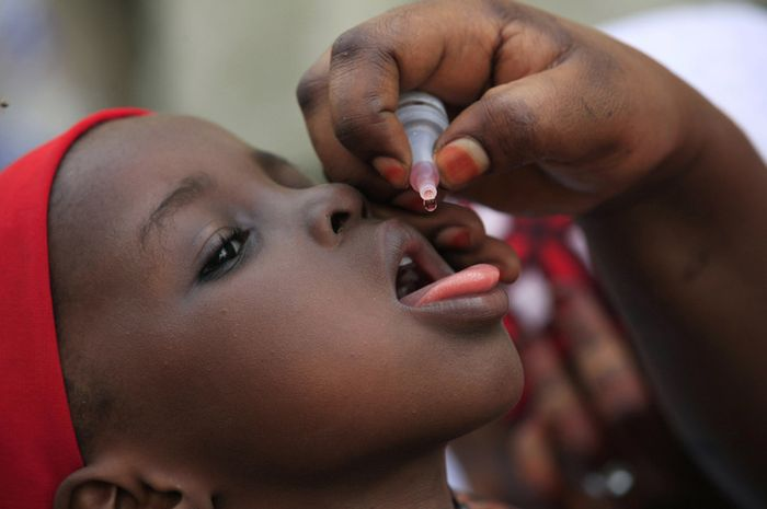 Seorang petugas kesehatan memberikan vaksin polio untuk anak di Kawo Kano, Nigeria. pada Minggu, 13
