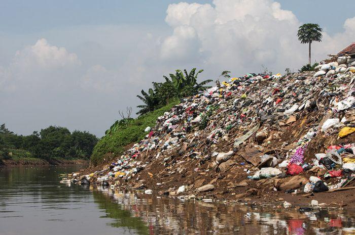 Tumpukan sampah menjadi benteng pemisah antara Ciliwung dan pemukiman warga. Kurangnya sarana tempat