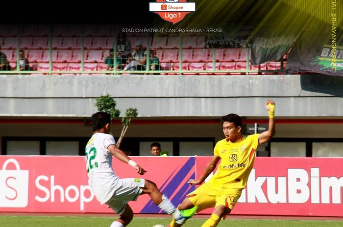 Penyerang Bhayangkara FC, Dendy Sulistyawan (kanan), berduel dengan bek Persebaya, Abu Rizal Maulana (kiri), pada laga pekan ke-17 di Stadion Patriot, Bekasi, Jawa Barat, Sabtu (31/8/2019).