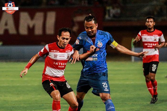 Pemain Madura United, Slamet Nurcahyo, berduel dengan bek Arema FC, Hamka Hamzah, pada laga pekan kesepuluh Liga 1 2019 di Stadion Gelora Madura, Sabtu (20/7/2019).