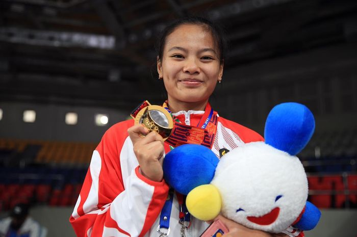 Lifter putri Indonesia, Windy Cantika Aisah, berpose dengan medali emas SEA Games kelas 49 kg di Ninoy Aquino Stadium, Manila.