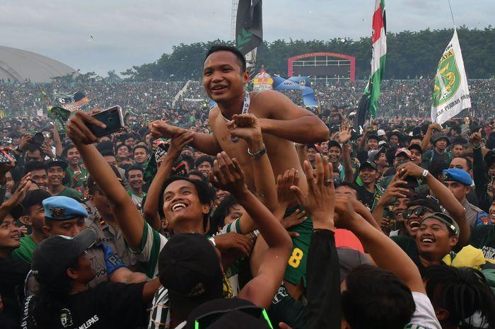 Pemain Persebaya Surabaya, Oktafianus Fernando, saat merayakan gelar juara Piala Gubernur Jatim 2020 di tengah kerumunan suporter Persebaya, Bonek, di Stadion Gelora Delta Sidoarjo, Kamis (20/2/2020).