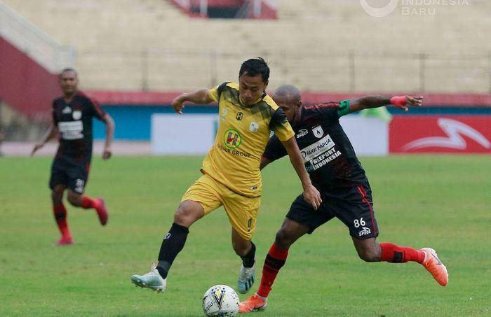 Pemain Persipura Jayapura, Boaz Solossa (kanan), saat berduel dengan pemain Barito Putera, Samsul Arif, dalam laga pekan ke-33 di Stadion Gelora Delta, Sidoarjo, Senin (16/12/2019).