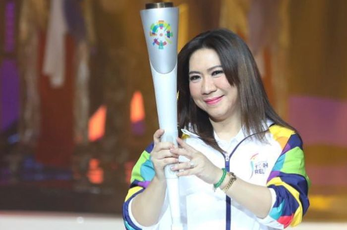 Susi Susanti memegang obor Asian Games 2018 di acara konser 100 Hari Asian Games