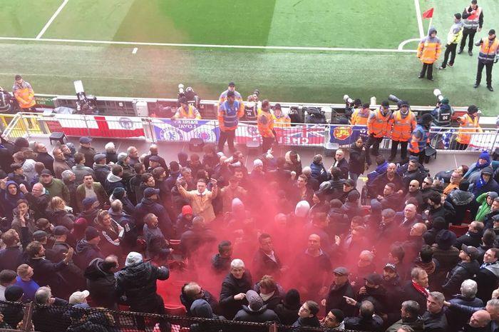 Fan Liverpool melemparkan bom asap ke arah tribune suporter Chelsea.