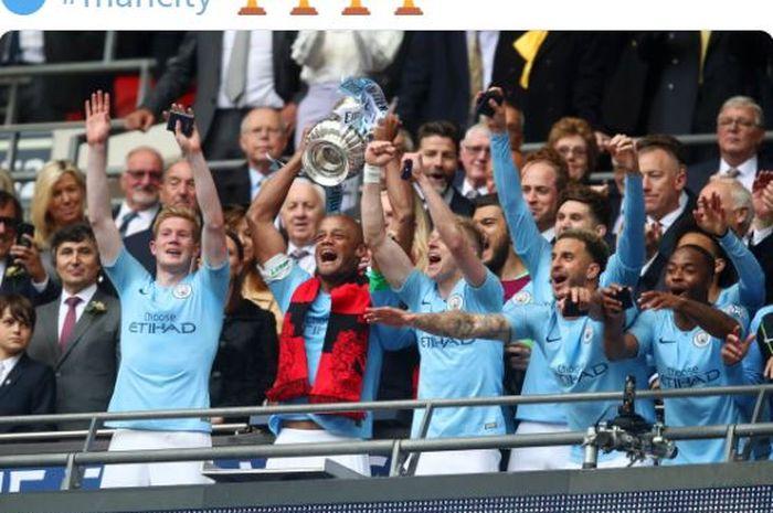Kapten Manchester City, Vincent Kompany, mengangkat trofi Piala FA usai mengalahkan Watford dalam laga final di Stadion Wembley, Sabtu (18/5/2019).