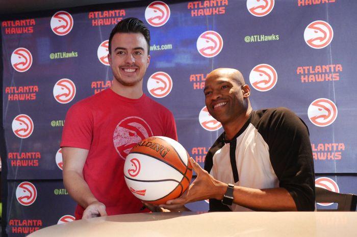 Pemain senior Atlanta Hawks, Vince Carter, menanda tangani bola basket milik seorang fans Hawks.