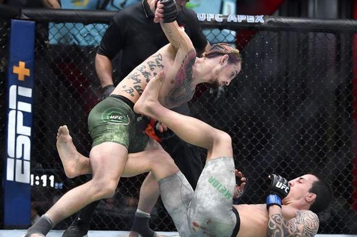 Aksi Bintang Baru, Sean O'Malley (berdiri) memberi pukulan penghabisan ke arah, Thomas Almeida (tiduran) pada UFC 260.