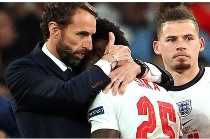 Pelatih timnas Inggris, Gareth Southgate, memeluk Bukayo Saka seusai laga final EURO 2020 kontra timnas Italia di Stadion Wembley, Minggu (11/7/2021).