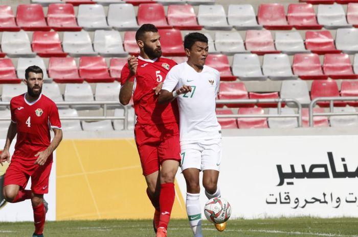Penyerang timnas Indonesia, Dedik Setiawan dijaga ketat oleh pemain timnas Yordania, Yazan Alarab, di Stadion King Abdullah II, Amman, Yordania, Selasa (11/6/2019).