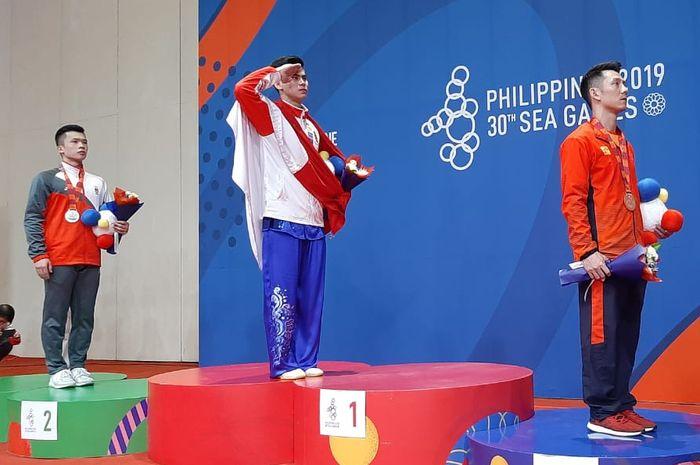 Edgar Xavier Marvelo berdiri di podium tertinggi setelah memenangkan dua emas bagi Indonesia pada cabang wushu, Selasa (3/12/2019).