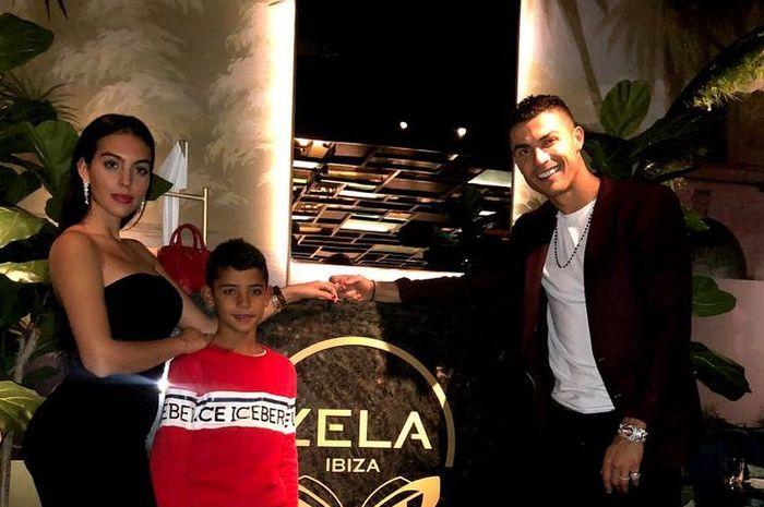 Cristiano Ronaldo Junior berada di antara Georgina Rodriguez (kiri) dan Cristiano Ronaldo merayakan