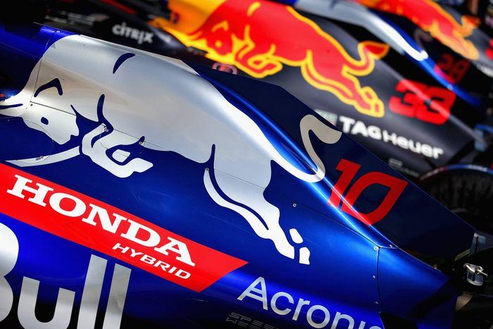 Mobil F1 Toro Rosso tahun 2018 berwarna biru terang, di sebelahnya mobil Red Bull dengan kelir biru gelap