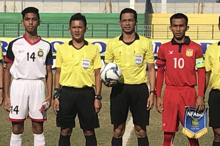 Kapten timnas U-16 Laos (merah) dan timnas U-16 Brunei (putih) berpose dengan perangkat pertandingan