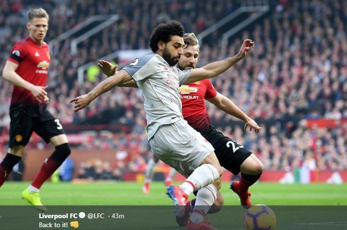 Penyerang Liverpool, Mohamed Salah (tengah), berduel dengan bek Manchester United, Luke Shaw, dalam laga Liga Inggris di Stadion Old Trafford, Minggu (24/2/2019).