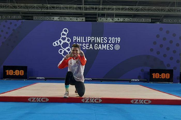 Lifter putra Indonesia, Deni, berpose dengan medali emas dari kelas 67 kg SEA Games 2019 di Ninoy Aquino Stadium, Selasa (3/12/2019).