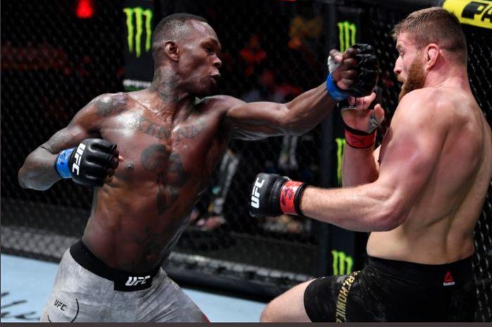 Juara kelas menengah UFC, Israel Adesanya, saat hendak memukul Jan Blachowicz yang terpojok sisi pagar. Kedua petarung saling terlibat bentrok pada ajang UFC 259 di UFC Apex, Las Vegas, Nevada, Amerika Serikat, Minggu (7/3/2021).