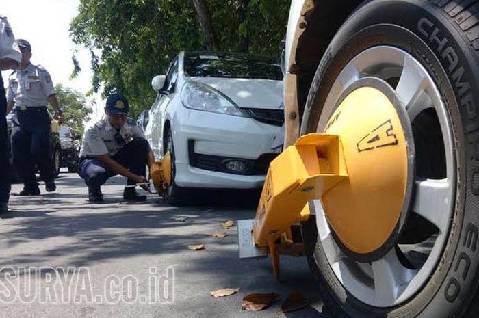 Petugas Dishub dan Polisi Lalu Lintas Polrestabes Surabaya menggembok mobil yang parkir sembarangan