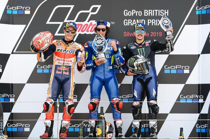 Dari kiri ke kanan, Marc Marquez, Alex Rins, dan Maverick Vinales berpose di podium MotoGP Inggris di Sirkuit Silverstone, Minggu (25/8/2019).