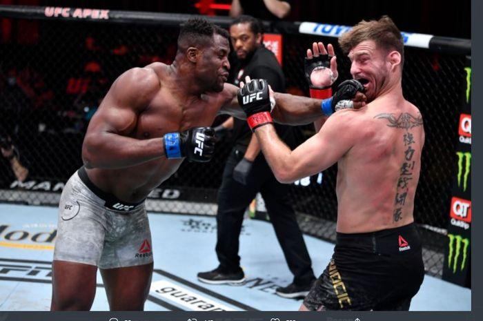 Francis Ngannou (kiri) saat memukul Stipe Miocic (kanan) pada ajang UFC 260, Sabtu (27/3/2021).
