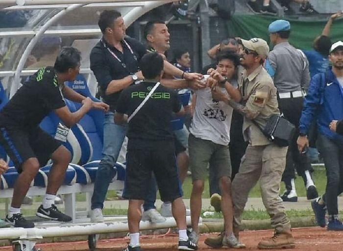 Pelatih Persib Bandung Miljan Radovic (kedua dari kiri) coba melindungi diri saat didatangi seorang suporter yang diduga hendak memukulnya di Stadion Si Jalak Harupat, Kabupaten Bandung, Kamis (7/3/2019) sore WIB, dalam duel Persib versus Persebaya Surabaya di Piala Presiden 2019.
