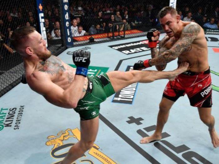 Conor McGregor (kiri) saat melakukan tendangan untuk menyeranga Dustin Poirier pada duel trilogi pada UFC 264 di T-Mobile Arena, Las Vegas, Nevada, AS, Minggu (11/7/2021).