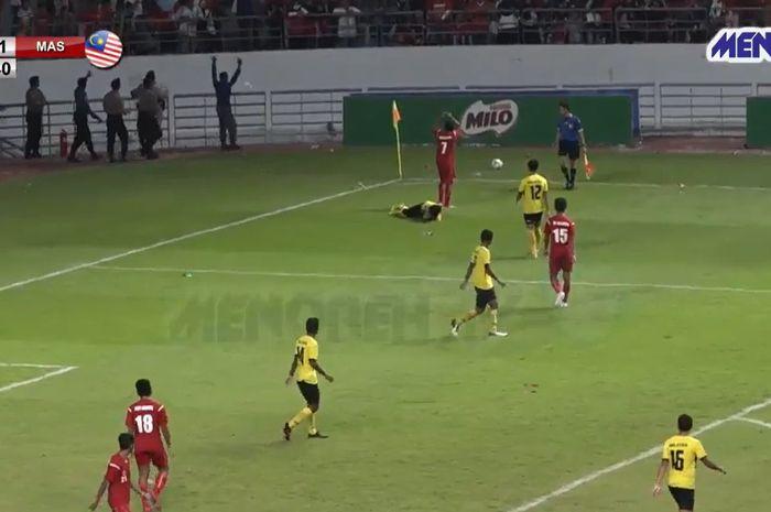 Salah satu pemain timnas pelajar U-18 Indonesia, Christian Rumbiak menampilkan aksi terpuji dengan melindungi pemain Malaysia dari lemparan botol penonton di Stadion Batakan, Jumat (22/11/2019).