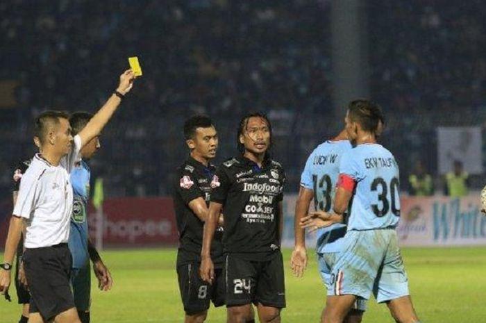 Pemain Persib Bandung Hariono (tengah) terkena kartu kuning.