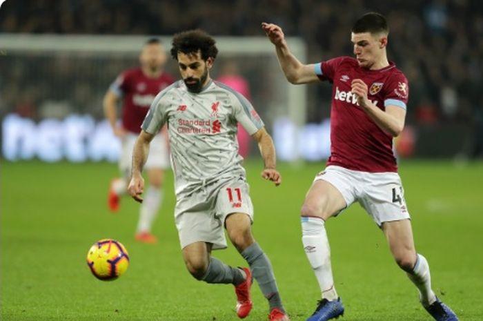 Gelandang West Ham United, Declan Rice (kanan), berduel dengan penyerang Liverpool, Mohamed Salah, dalam laga Liga Inggris di London Stadium, Senin (4/2/2019).