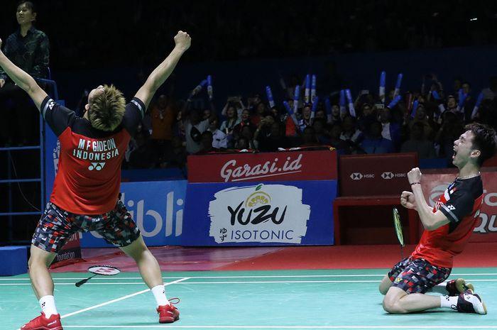 Pasangan ganda putra Indonesia, Marcus Fernaldi Gideon/Kevin Sanjaya Sukamuljo, bereaksi setelah memastikan diri menjadi juara Indonesia Open 2019 di Istora Senayan, Jakarta, Minggu (21/7/2019).