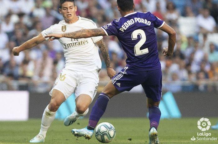 Gelandang serang Real Madrid, James Rodriguez, berusaha melewati hadangan pemain Real Valladolid, Pedro Porro, ketika kedua tim bertemu pada pekan kedua La Liga Spanyol, Ahad (25/8/2019) di Stadion Santiago Bernabeu, Madrid.