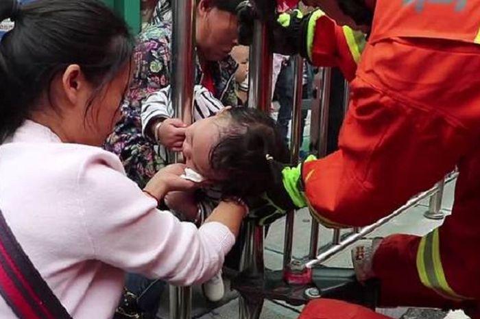 Kepala seorang anak di China tersangkut di pagar pembatas jalan